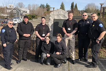 Image of eight members of the Tulalip police smiling in front of a farm