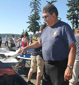 Tulalip Tribal Police Department officers in the community, serving up barbecued meals.