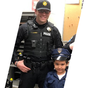 Tulalip Tribal Police Department officer with young child in police uniform. header sliding image.