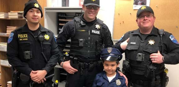 Three officers of Tulalip Tribal Police with young child in uniform, experience chief for a day mobile image.