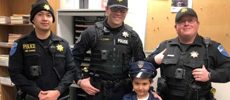 Three officers of Tulalip Tribal Police with young child in uniform, experience chief for a day tablet image.